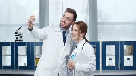 коллега : smiling female and male doctors talking to a smartphone in clinic