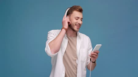 прослушивание : man in headphones listening music on smartphone Стоковые видеозаписи