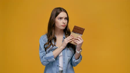 ninguém : girl eating chocolate isolated on yellow background Vídeos