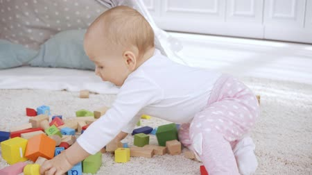 pillow block : cute toddler kid playing with multicolored wooden blocks on carpet Stock Footage