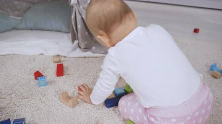 pillow block : baby crawling on all fours on wooden board among wooden multicolored cubes near baby wigwam and rocking horse