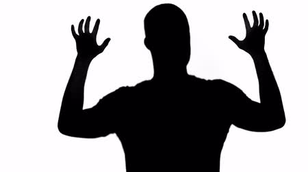 anonyme : Silhouette of man slowly scratching isolated on white Vidéos Libres De Droits