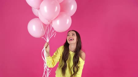 kıpkırmızı : studio shot of happy young woman holding pink air balloons and turning around on crimson background