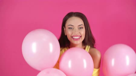 crimson : studio shot of happy young woman holding pink air balloons on crimson background