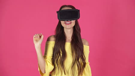 kıpkırmızı : studio shoot of excited young woman in virtual reality headset gesturing isolated on crimson