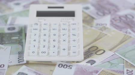 disperso : selective focus of scattered euro banknotes and calculator