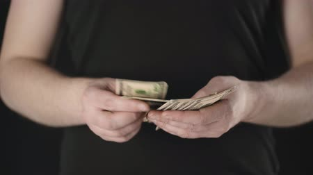 banknotlar : cropped view of man counting dollar banknotes isolated on black Stok Video