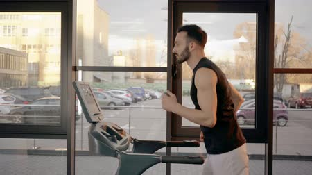 kimerül : Side view of sportsman in white shorts running on treadmill