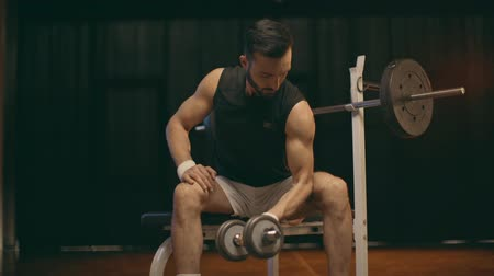 esportivo : Concentrated muscular sportsman in white shorts doing biceps curls and lowering dumbbell Stock Footage