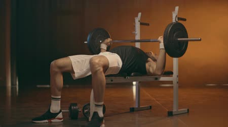 powerlifter : Powerlifter in white shorts and sneakers doing bench press