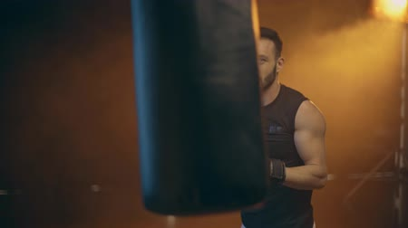 átlyukasztás : Concentrated boxer with beard in boxing gloves training with punching bag