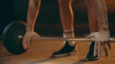 powerlifter : Partial view of powerlifter in black sneakers raising barbell Stock Footage
