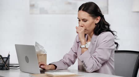 coughing : businesswoman sitting in modern office