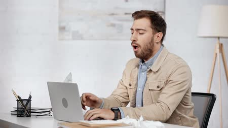 coughing : bearded businessman typing on laptop Stock Footage