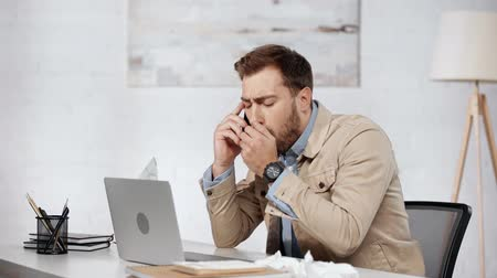 dokular : sick businessman using laptop, talking on smartphone, sneezing, taking tissue and coughing in office