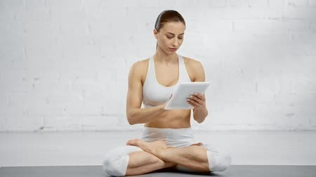penteado : focused woman sitting in lotus pose, using digital tablet, smiling and meditating with closed eyes