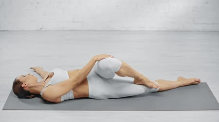 zihinsel : barefoot woman stretching on yoga mat and practicing mritasana