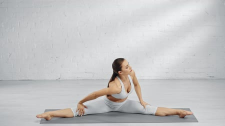 sznurek : woman doing twine, stretching, practicing upavistha konasana, smiling and showing namaste sign