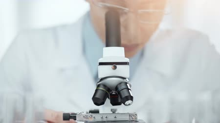 clínico : selective focus of african american scientist in glasses using microscope with back light Stock Footage