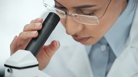 a medicare : close up view of focused african american scientist in glasses using microscope