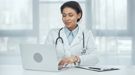 clínico : smiling american american doctor with stethoscope using laptop