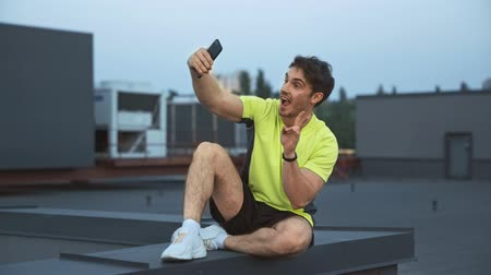 гримаса : handsome sportsman sitting on rooftop, holding smartphone