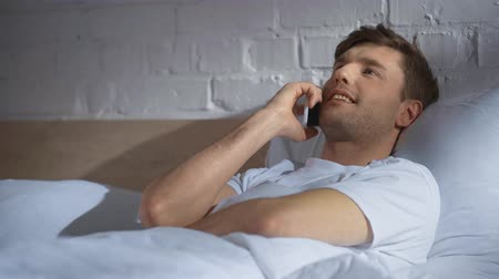 speaking : man in white t-shirt lying in bed, talking on smartphone and laughing in the morning Stock Footage