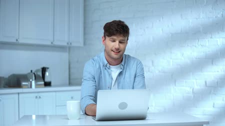 drinking coffee : cheerful freelancer using laptop