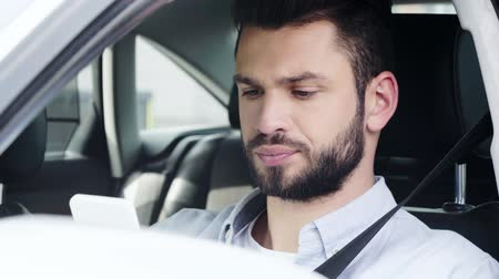sürücü : selective focus of dissatisfied man sitting in car and using smartphone Stok Video
