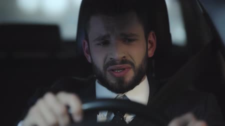 auta : selective focus of upset bearded man crying while driving car