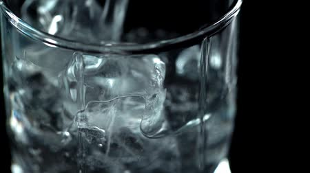 hydratace : cold water pouring ice cubes isolated on black