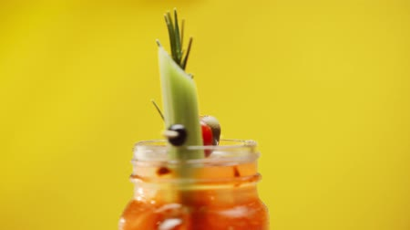 fogpiszkáló : selective focus with bloody mary cocktail spinning on yellow Stock mozgókép
