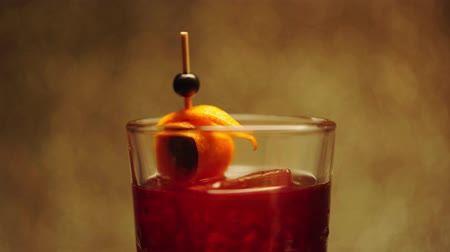 fogpiszkáló : toothpick with orange peel in spinning alcohol drink on brown Stock mozgókép