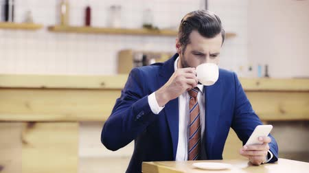 csészealj : businessman drinking coffee and using smartphone