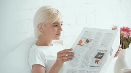 газета : beautiful girl in pajamas reading newspaper, drinking coffee and smiling in bed