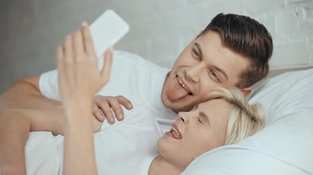 dinlenmek : beautiful couple sticking tongue out, smiling, kissing and taking a selfie Stok Video