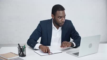 носить : african american businessman sitting at workplace in office Стоковые видеозаписи