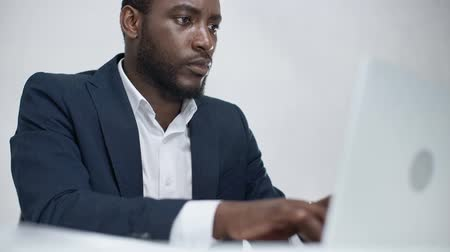 desgaste formal : attentive african american businessman using laptop while sitting at workplace in office