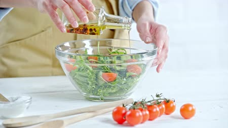 olive oil pour : Cropped view of woman pouring olive oil in vegetable salad near ingredients on table