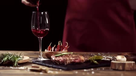 перец чили : Cropped view of man pouring wine in glass near meat steak and ingredients on table isolated on black