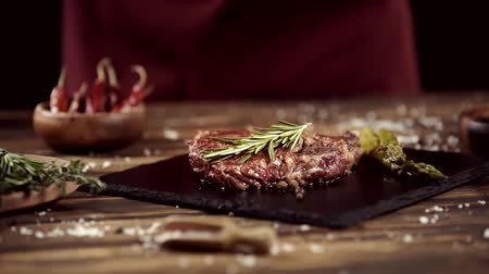 poivre noir : falling rosemary on delicious meat steak on table with ingredients