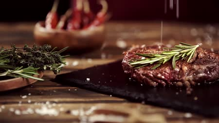 oregano : falling salt on delicious meat steak on table with ingredients Stock Footage