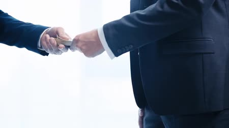 desgaste formal : cropped view of businessman giving dollar banknotes and shaking hands with business partner