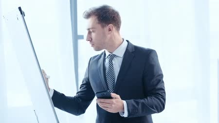 flip chart : handsome businessman using smartphone and writing on flipchart in office
