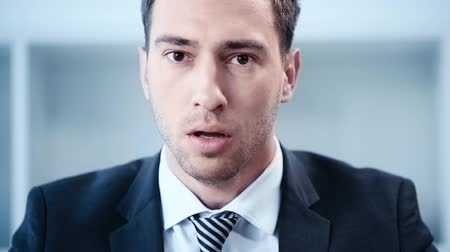 носить : slow motion of shocked businessman touching tie while looking at camera