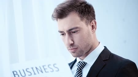 газета : serious, discouraged businessman reading business newspaper in office