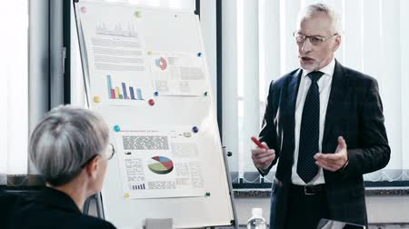 marker pen : selective focus of handsome businessman in glasses talking near coworker while standing near flipchart with charts and graphs