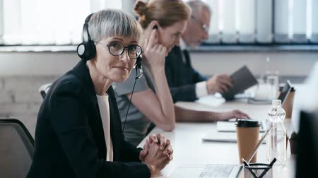 телемаркетинг : happy woman in glasses in headset with clenched hands near coworkers in office