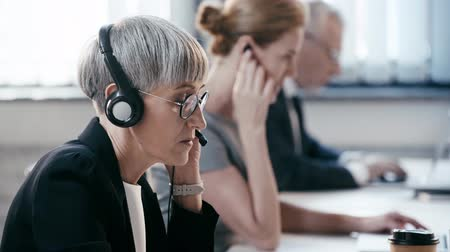 телемаркетинг : selective focus of businesswoman in headset talking while working near coworkers