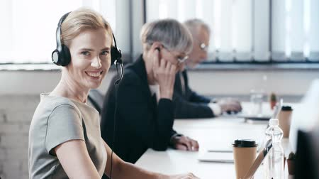 телемаркетинг : cheerful woman in headset smiling while looking at camera near coworkers in office Стоковые видеозаписи